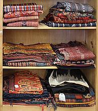 (lot of 27) Three shelves of ethnographic textiles, including Indonesian cotton ikats, and embroideries together with Syrian clothing