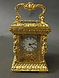 An ornate brass carriage clock with 'Trigona'