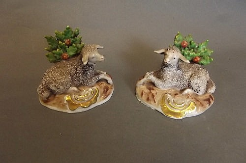 A pair of C19th porcelain models of recumbent