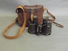 A pair of WWI field glasses in a leather case by