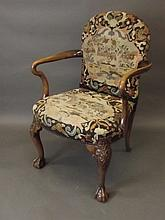 A George I style walnut elbow chair on carved