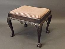 A Georgian style carved mahogany footstool on ball