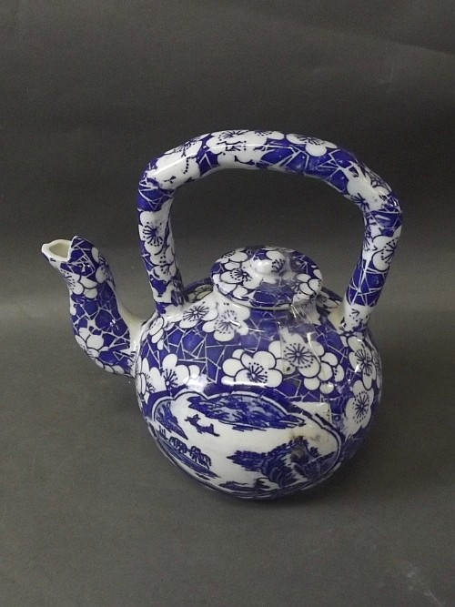 A blue and white Chinese teapot with floral and