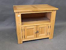 A solid oak two door cupboard with open upper