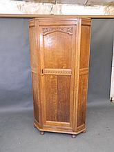 An Edwardian carved oak hall cupboard with canted