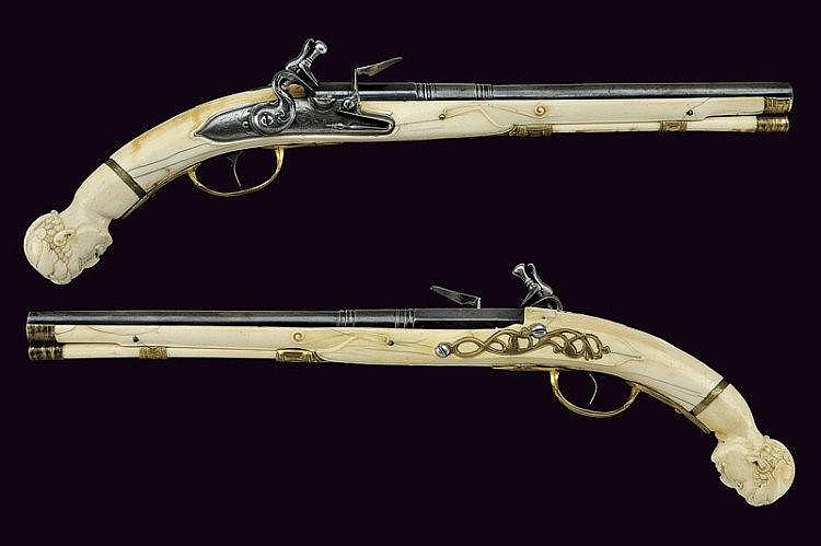 An extremely rare pair of flintlock pistols with carved stocks