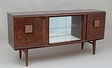 Vintage Retro : a 1950/60's afrormosia and teak breakfront sideboard / cocktail cabinet having the unusual mirror backed rotating glased front cupboard ( to one side ) and a mirror backed melamine glasses, 5 bottle stands etc to the other flanked by