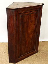 An early 19thC flame mahogany panelled hanging corner cupboard, the door opening to reveal four shelves with and a smaller shelf 40