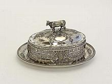 A late 19thC / early 20thC  silver plate and cut glass butter dish, the silver plate base with central cut glass oval dish with silver plate cover, the handle formed as a cow . 8 1/4