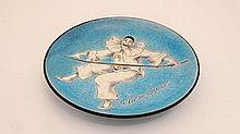An early 20thC enamelled decorative dish depicting Pierrot holding a balancing stick on a crackle glazed turquoise ground. Signed G. van der Straeten to front and marked L. Simonet Paris to reverse. Diameter 8