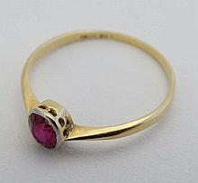 An 18ct gold ring with platinum set ruby to top