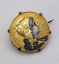 A gilt metal brooch set with a gilded French coin in a captive mount approx 1