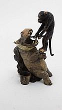 A cold painted bronze novelty figure depicting a monkey about to remove a tooth from a bandaged hippopotamus 2 1/2