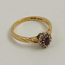 An 18ct gold ring set with central ruby bordered by 12 diamonds flaked by a further diamond to each shoulder.