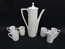 A Retro Portmerion Totem pattern tea/coffee set by Susan William-Ellis. White glaze. Includes Coffee/tea pot, five cups and milk jug. Teapot 13'' high, cups 3 1/4'' high, milk jug 4'' high.