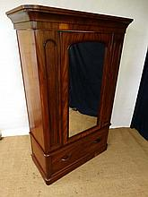 A Victorian mahogany single wardrobe with mirrored door over single drawer  opening to reveal hanging rail and pegs within. 52