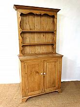 An early 20thC narrow pine dresser with open plate rack on a two door cupboard base with porcelain handles 39 1/2