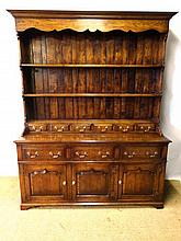 A contemporary Georgian Oak Style Dresser and open plate rack , having 6 short drawers to top over a base of 3 drawers with 3 cupboards under , 65