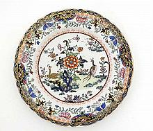 An Ironstone plate decorated in Oriental style. Decorated with floral and foliate detail with birds and gilt detail to rim. Stamped to base. 10 1/4'' diameter.