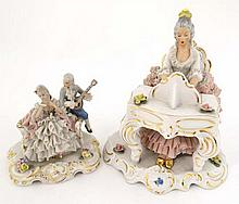 Dresden figurines depicting figures with glazed netting detail comprising a female seated at a piano, together with a figure group of a pair of galants, the female seated, the male with musical instrument. Blue printed marks to base. Heights 8