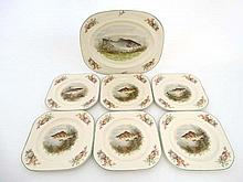 A set of Wood's Ivory Ware fish plates consisting of six smaller plates together with one large serving plate. The centres decorated with fresh water fish such as trout and perch. Serving plate 14'' x 11''. Small plates 8 1/2'' x 8 1/2''.