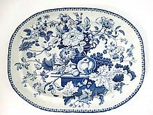 A 19thC blue and white large dish with a small bluebell style border, within is a vase of flowers and foliage standing on a small table surrounded by fruits. No makers marks except '20' impressed into the base. size 20 3/4