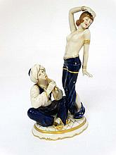A Royal Dux Art Deco figure group depicting a half naked female in exotic dance pose while a turbaned flute player sits at her feet. Model No. 3037. Costume in cobalt and gilt. Printed, impressed and lozenge mark to base. Height 12