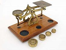 Postal scales : A set of brass oak postal scales having 4 weights from 2 oz to half oz . 7