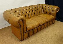 A tan leather button back Chesterfield style