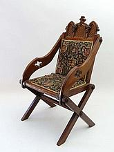 A 19thC oak Glastonbury chair of Neo Gothic style