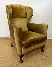 An early 20thC wingback upholstered armchair with