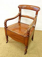 A Victorian walnut commode with open arms and