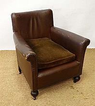 A 1920's child's leather club armchair with brass