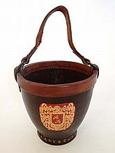 A leather and brass ice bucket with applied gold