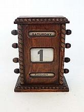 An early 20thC oak perpetual calendar with beaded