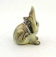 A pottery figurine depicting a rabbit washing.