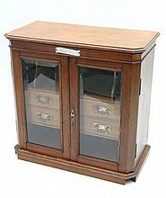 A 1907 blonde oak fine quality smokers cabinet