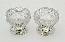 A pair of cut glass salts on silver pedestal bases