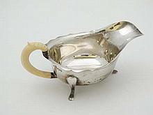 A silver sauce boat with ivory handle , hallmarked