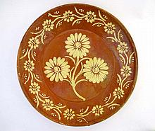 A Slipware terracotta charger with cream floral