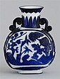 OVERLAY GLASS BOTTLE VASE In pilgrim flask form with peony, lotus, chrysanthemum, and prunus design in blue on a milk-white ground....