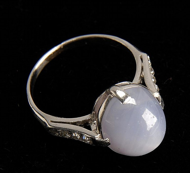 WHITE GOLD, STAR SAPPHIRE, AND DIAMOND RING with oval star sapphire cabochon flanked by eight diamonds. Size 6¾.