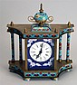 ENAMEL AND BRASS SPRING-DRIVEN CLOCK. Height 9¼