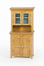 CHILD'S STEP-BACK CUPBOARD In pine with yellow grain-painted decoration. Molded carved top over two glass doors with milk glass pull..