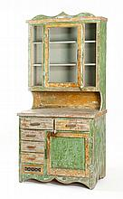 COUNTRY HUTCH In pine under distressed green, white and yellow paint. Upper section with shaped cornice over paneled glass door flan...