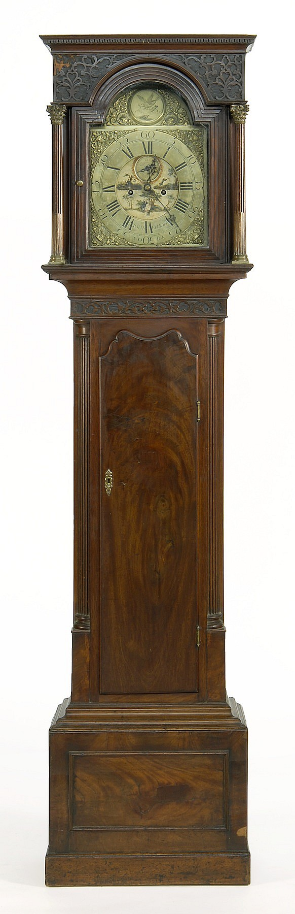 ENGLISH TALL-CASE CLOCK By John Elliott. In walnut and walnut veneers. Bonnet with modified dental molding above applied leaf carvin...