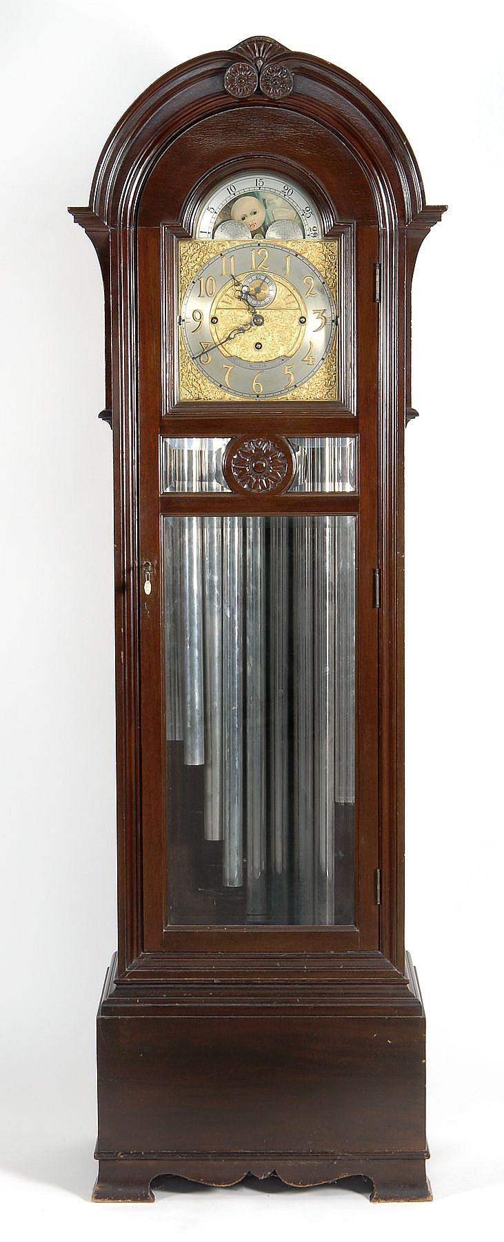 WALTHAM NINE-CHIME TALL-CASE CLOCK Mahogany case with shell crest and beveled glass door. Moon phase dial. Brass numerals on burnish...