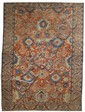 ORIENTAL RUG: HERIZ Abrashed brick-red field contains several bold stylized elements in blue, salmon pink, faded green and gold. Fad...