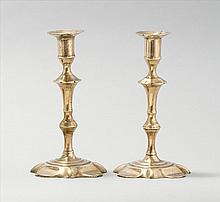 PAIR OF QUEEN ANNE BRASS CANDLESTICKS With turned stems and lobed bases. Height 8.25
