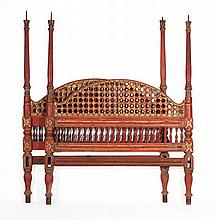 CARVED WOODEN PERSIAN BED Painted red with gilt highlighting. Arched headboard and footboard with pierced and floral rosette design....